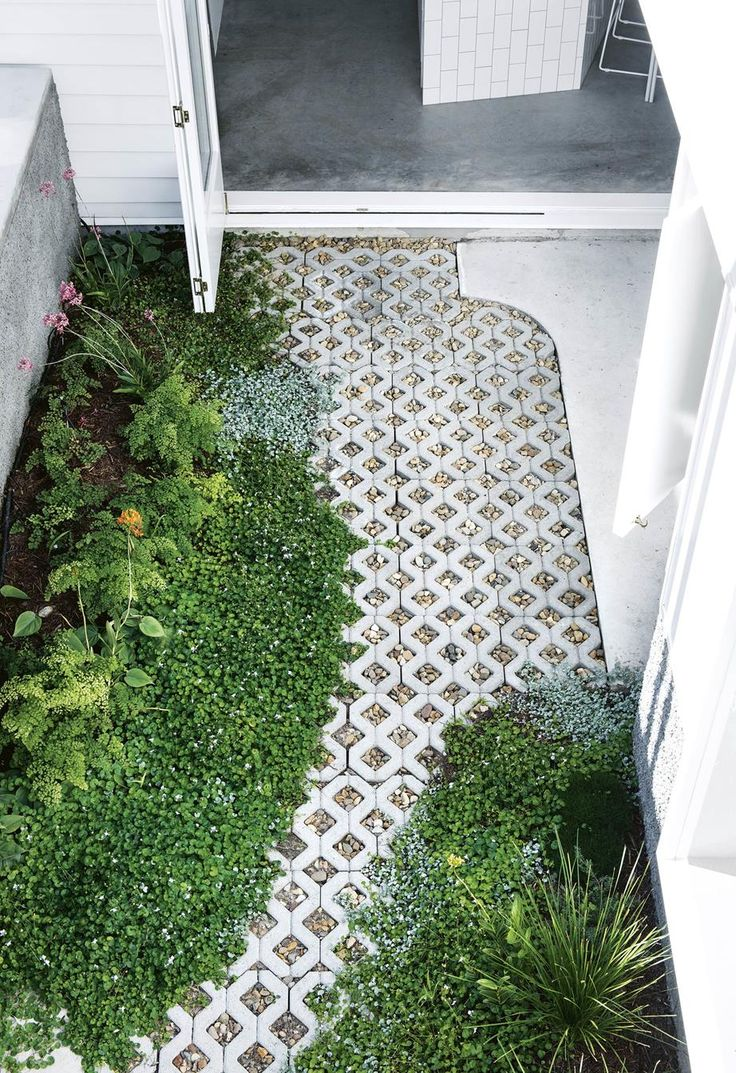 Garden courtyard with lush plants and grass pavers. | Renovating with white: thi...