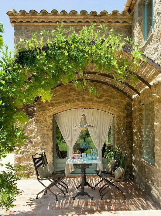Arched pergola over stone farmhouse patio dining area. Romantic French Country G...