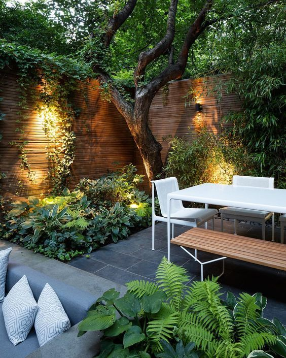 a contemporary townhouse garden with stone tiles, minimalist furniture of wood a...