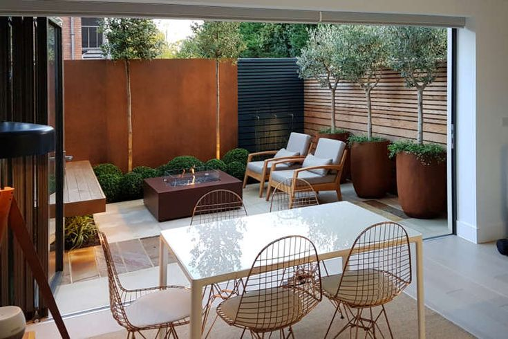Townhouse garden design by Garden Club London with built in seating, corten feat...