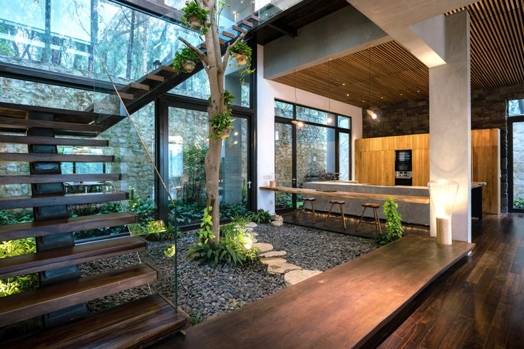 Indoor courtyard garden surrounded with a staircase that leads to the upper bedr...