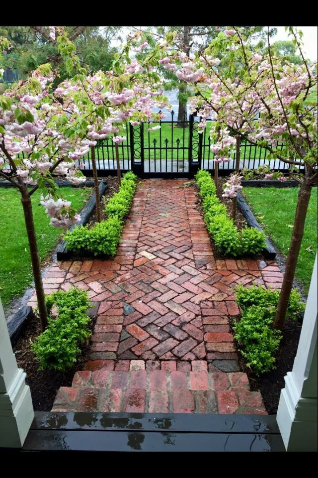 Classic inviting entrance, black fence, aged brick in herringbone pattern, small...